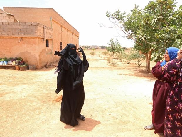 Mulher com o niqab (véu preto que cobre todo o rosto, menos os olhos), de uso obrigatório em cidades controladas pelo Estado Islâmico (Foto: Rodi Said/Reuters)