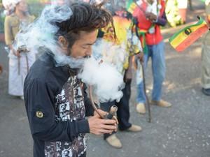 Um rastafari chamado Bongho Jatusy fuma maconha em frente a museu da erva na Jamaica (Foto: AP Photo/David McFadden)