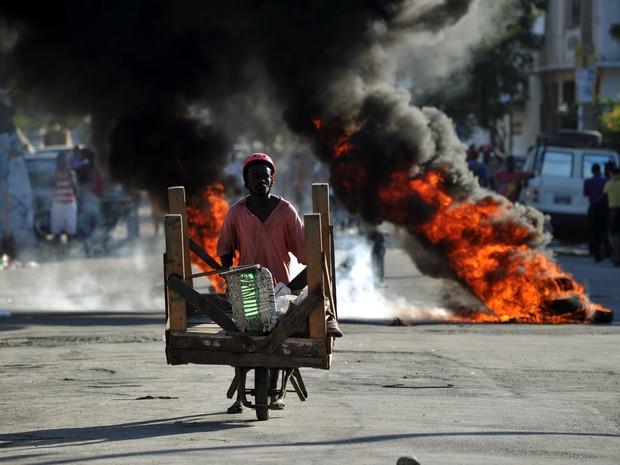 Homem anda em meio às chamas de pneus queimados durante protesto em Porto Príncipe (Foto: Hector Retamal/AFP)