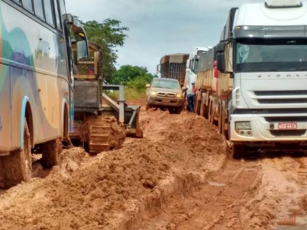 Imagem mostra ônibus sendo puxado por um trator em estrada com atoleiro (Foto: Associação dos Municípios do Araguaia/ Divulgação)