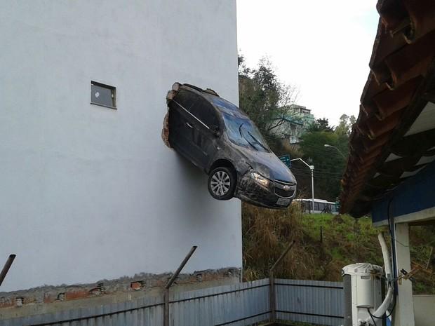 Carro ficou pendurado em Colatina, no Noroeste do Espírito Santo, após homem acelerar na garagem (Foto: Divulgação/Polícia Militar e Corpo de Bombeiros)