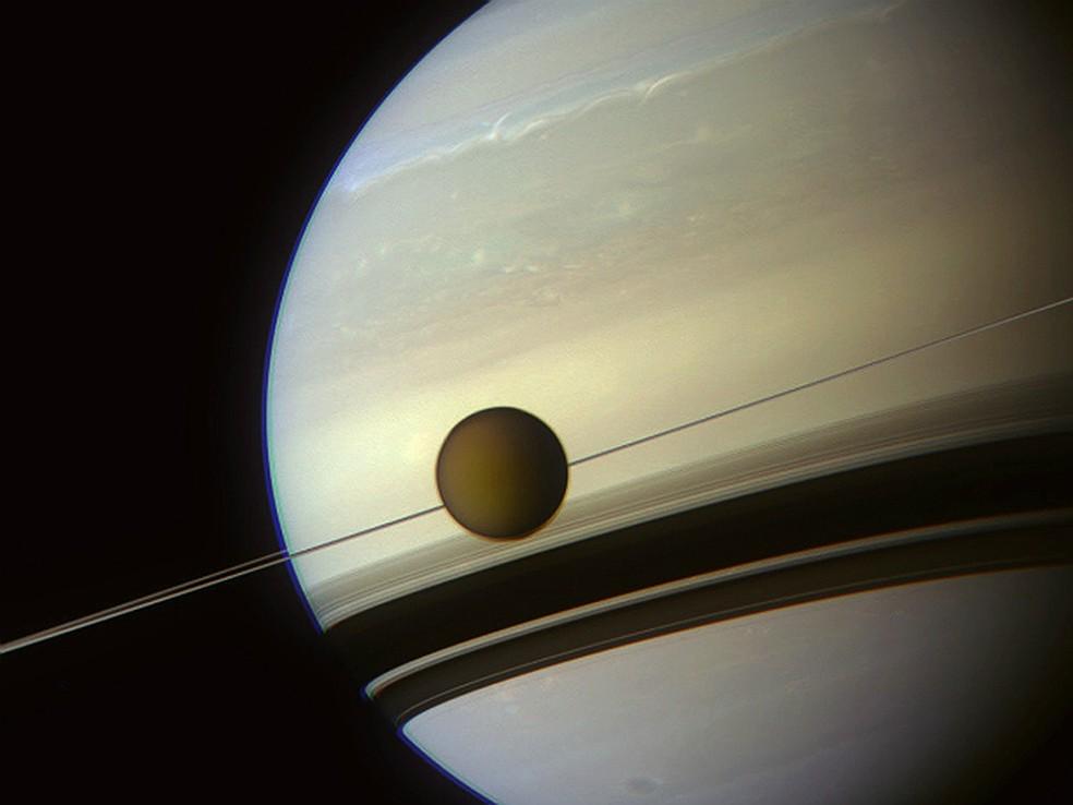 Maior lua de Saturno, Titã orbita o planeta em imagem captada pela sonda Cassini, da Nasa. Os anéis de Saturno são planos e vistos como uma linha fina, parecendo 'espetar' Titã. Análises recentes indicam que a lua do planeta pode ter vastos oceanos (Foto: NASA/JPL-Caltech/Space Science Institute/J. Major)