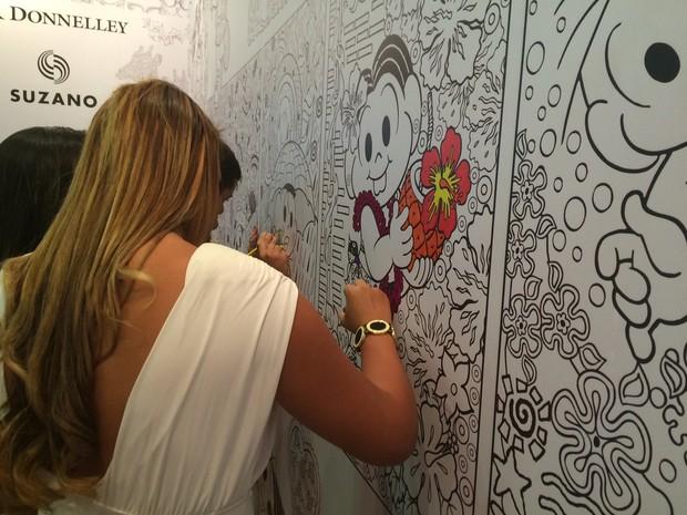 Jovem pinta parede de stand da Bienal do Rio (Foto: Gabriel Barreira / G1)