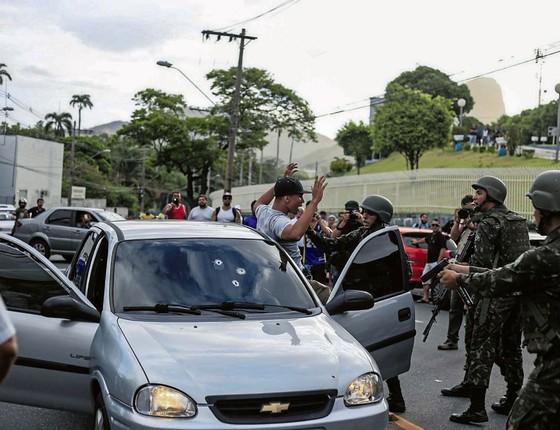 Soldados do Exército revistam homem durante patrulha.Os militares tiveram de assumir o papel da polícia,mas eram pouco (Foto:  Marlon Max/TRÊS16/ÉPOCA)