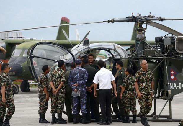 Oficiais nepaleses se reúnem em frente a aeronave que avistou os destroços de helicóptero dos EUA que caiu na terça-feira (12) (Foto: Prakash Mathema/AFP)