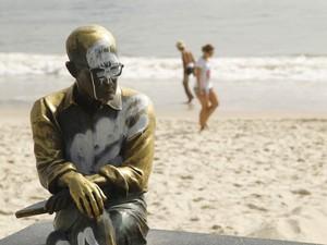 Estátua de Carlos Drummond de Andrade amanhece pichada na manhã de Natal na Praia de Copacabana, na Zona Sul do Rio de Janeiro. (Foto: Marcelo Carnaval/Agência O Globo)