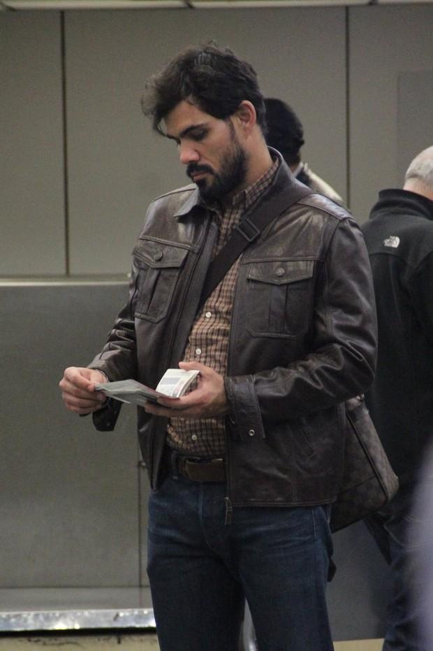 Juliano Cazarré confere seu passaporte (Foto: Rodrigo dos Anjos/Ag News)
