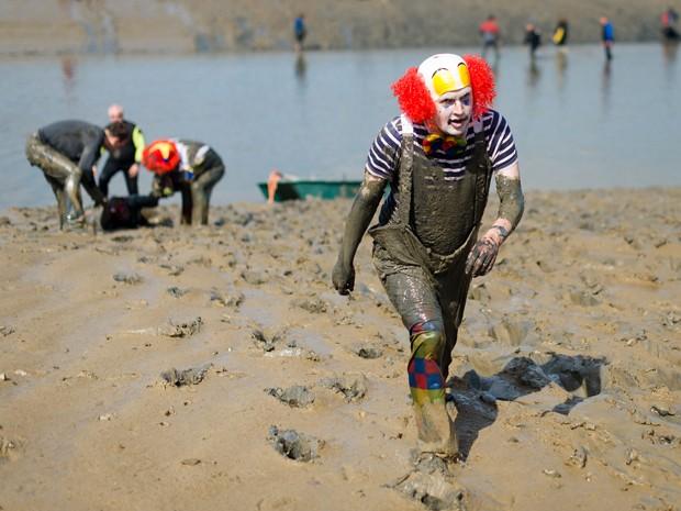 Homem vestido de palhaço deixa competidores para trás na anual corrida na lama em Maldon, na Inglaterra (Foto: Leon Neal/AFP)