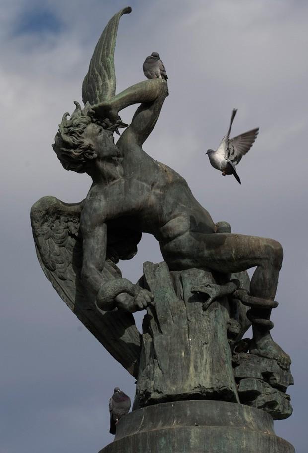 Pombas parecem assustar a estátua de Lúcifer no parque do Retiro, em Madri (Foto: Paul White/AP)