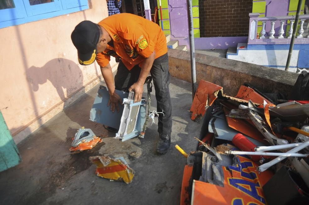 Membro da agência nacional de busca e resgate da Indonésia segura destroços do helicóptero que caiu em Java (Foto: Associated Press)