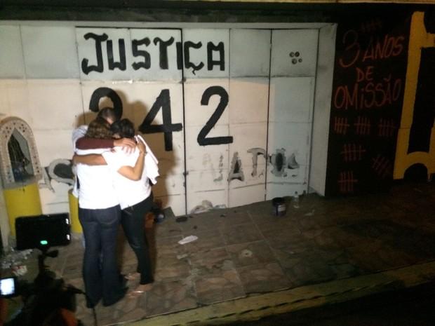 Familiares de vítimas se abraçam em frente à antiga porta de entrada da boate Kiss (Foto: Daniel Favero/G1)