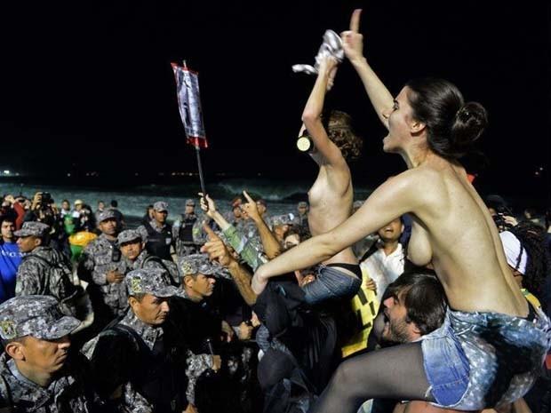 Manifestantes subiram nos ombros de colegas e, com os seios à mostra, provocaram fiéis que acompanhavam shows da Jornada Mundial da Juventude, em Copacabana (Foto: Tasso Marcelo/ AFP Photo)