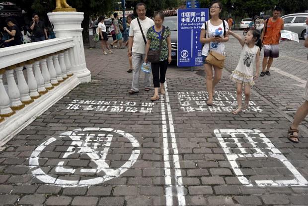 Um dos lados é destinado para quem está utilizando o celular enquanto caminha, e o outro, para quem não usa o aparelho (Foto: AP)