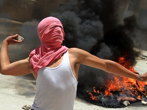 jovem palestino atira uma pedra em direção a soldados israelenses durante confrontos em Kafr Aqab, após uma incursão do Exército israelense na cidade (Foto: Abbas Momani/AFP)