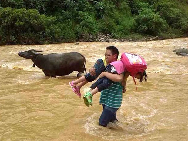 Professor na China enfrenta rio para ajudar alunos na travessia e levá-las à escola  (Foto: Imaginechina)