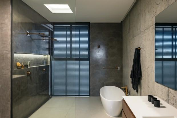 Banheiro. Com revestimento da Cement Design, tem tons sóbrios e metais dourados (Foto: Leonardo Finotti / Editora Globo)