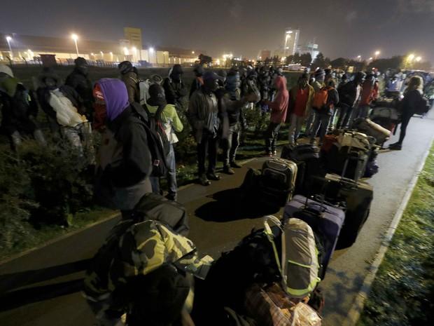 Imigrantes deixam o acampamento de Calais durante a madrugada na França (Foto: Philippe Wojazer/Reuters)