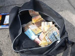 Dinheiro roubado da agência bancária foi encontrado em posse dos suspeitos (Foto: Walter Paparazzo/G1)