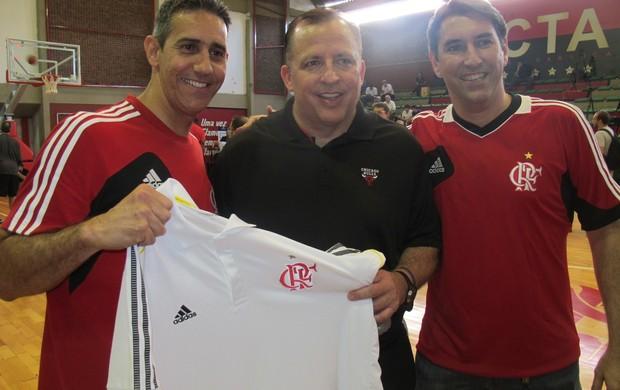 Ao lado do supervisor André Guimarães, o técnico do Flamengo, José Neto, ofereceu a Tom Thibodeau uma camisa do clube rubro-negro (Foto: Marcello Pires)