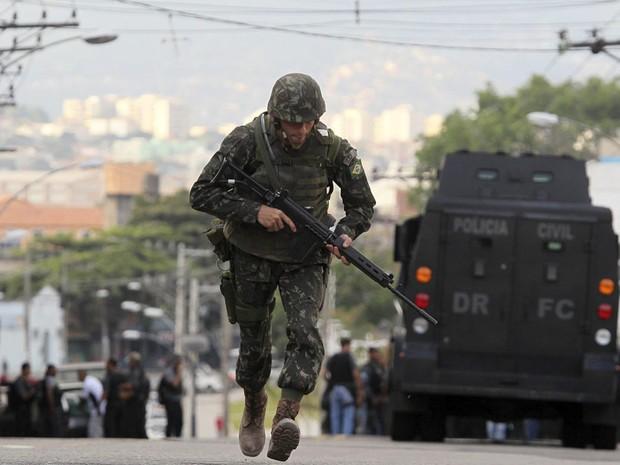 Soldado do Exército corre no Complexo do Alemão, no começo da manhã deste domingo.  (Foto: Sergio Moraes/Reuters)