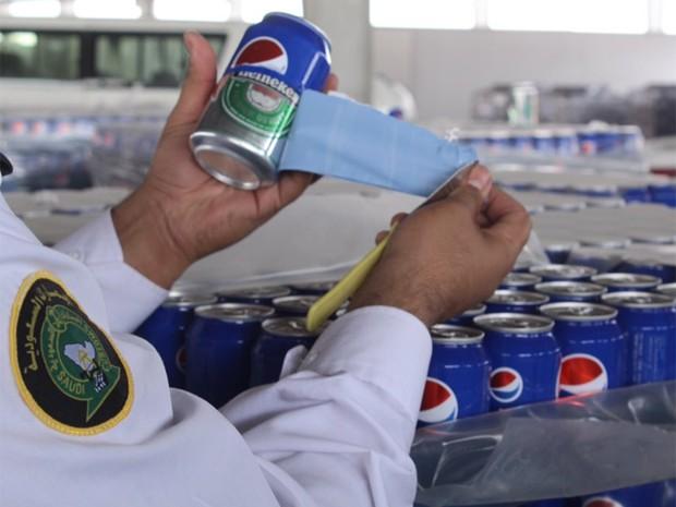 Oficial da alfândega mostra lata de Heineken disfarçada de Pepsi, apreendida em fronteira da Arábia Saudita (Foto: Reprodução/Twitter/KSA Customs)