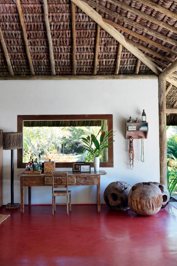Aparador | O móvel oriundo de Minas Gerais serve de bar e escritório e fica em um canto do estar. Ao lado, no piso de cimento queimado, esculturas de Elma Chaves, criadas a partir de raízes de árvores (Foto: Evelyn Müller / Living Inside)