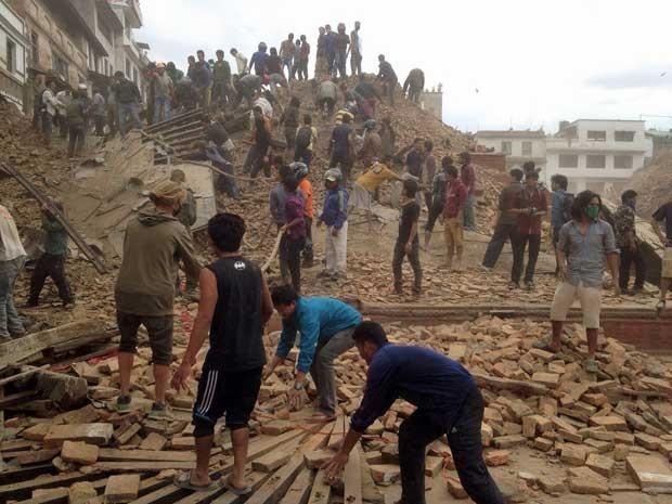 Voluntários ajudam com o trabalho de resgate no local de um edifício que desabou após um terremoto em Katmandu. (Foto: Niranjan Shrestha / AP Photo)