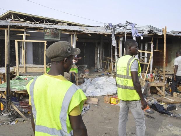 Pessoas observam os danos após ataque de mulher-bomba em mercado de Maiduguri, na Nigéria, na terça-feira (10) (Foto: AP Photo/Jossy Ola)