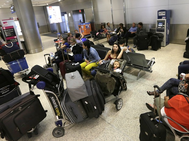 Passageiros esperam para embarcar no Aeroporto Internacional de Miami na noite de terça-feira (25) (Foto: AP Photo/Alan Diaz)