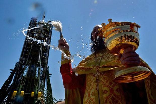 Sacerdote ortodoxo russo abençoa a nave Soyuz YMA1-13M, que deve decolar nesta quarta-feira do Cazaquistão rumo ao espaço (Foto: Kirill Kudryavtsev/AFP)