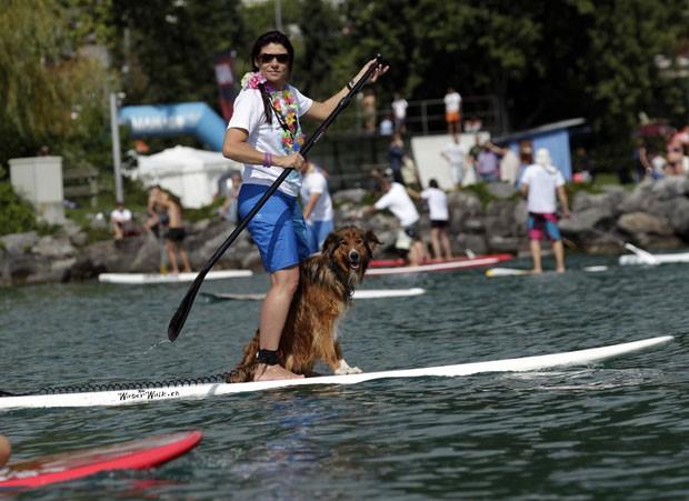 Mulher e cão surfam em prancha stand up durante evento de caridade no Lago Leman, na cidade suíça de Montreux, neste domingo (2). Eles participavam de um evento de uma ONG para angariar fundos para programas de educação infantil no Peru (Foto: Denis Balibouse/Reuters)