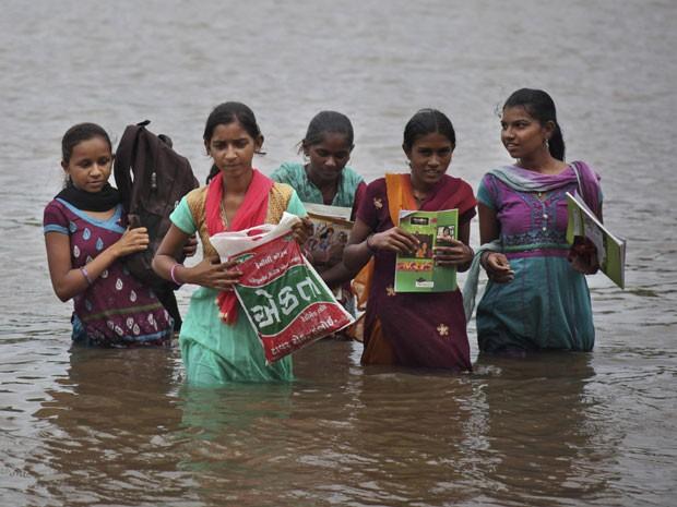 Estudantes atravessam rio levando o material escolar em sacos plásticos (Foto: Ajit Solanki/AP)