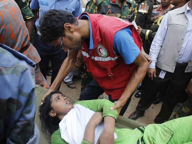 Equipes de resgate confortam uma sobrevivente, que estava presa nos escombros do edifício que desabou em Bangladesh. (Foto: Andrew Biraj / Reuters)