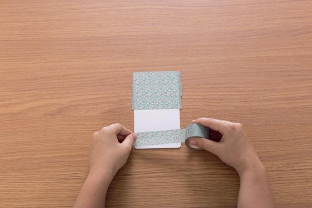 3. Cubra a metade superior (9 cm) com a fita adesiva. Deixe um espaço em branco de 6 cm. E termine a colagem na parte inferior que sobrou (3 cm). (Foto: Bruno Marçal / Editora Globo)
