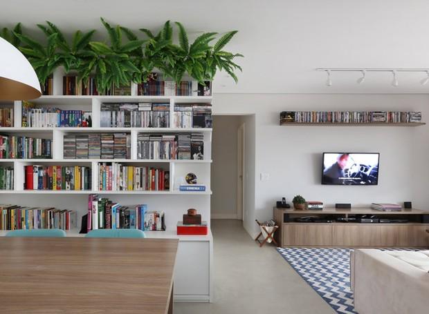 A entrada do lar ganhou uma estante de nichos vazados e personalizada que foi projetada e executada pelo escritório GF Projetos. No topo, samambaias artificiais da loja K&D dão um toque verde ao ambiente (Foto: Mariana Orsi/Divulgação)