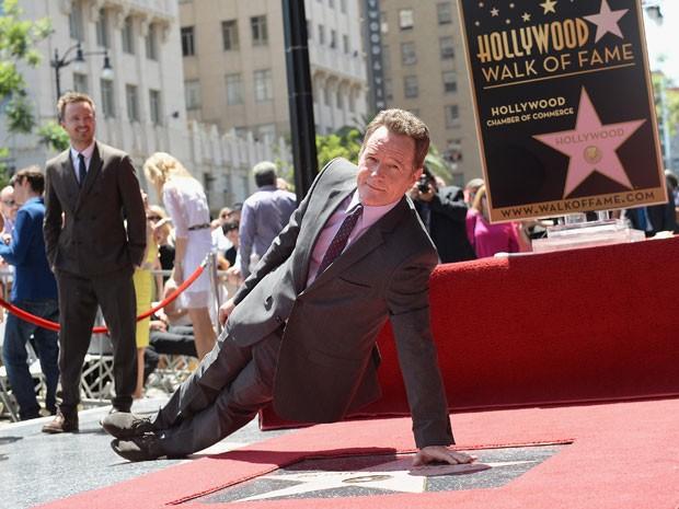 Observado por Aaron Paul, o Jesse de 'Breaking bad', Bryan Cranston, que vive Walter White, protagonista da série, faz flexão lateral ao receber estrela na Calçada da Fama de Hollywood (Foto: Michael Buckner/Getty Images/AFP)