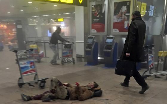 Um homem machucado espera por socorro no aeroporto de Bruxelas, na Bélgica. A polícia fechou o aeroporto por motivos de segurança após o atentado matar dezenas de pessoas (Foto: Ketevan Kardava/ Georgian Public Broadcaster/AP)