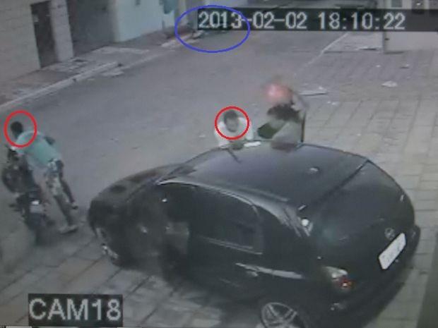 Warllyn (de branco) pega a arma na mão da adolescente. Enquanto isso, Max (de verde) se prepara para fugir. Vítima está caída no canto superior da imagem (Foto: Reprodução/SSP)
