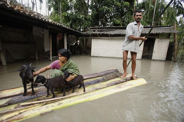 Manoranjan Kalita usou jangada para transportar mulher e animais. (Foto: Anupam Nath/AP)
