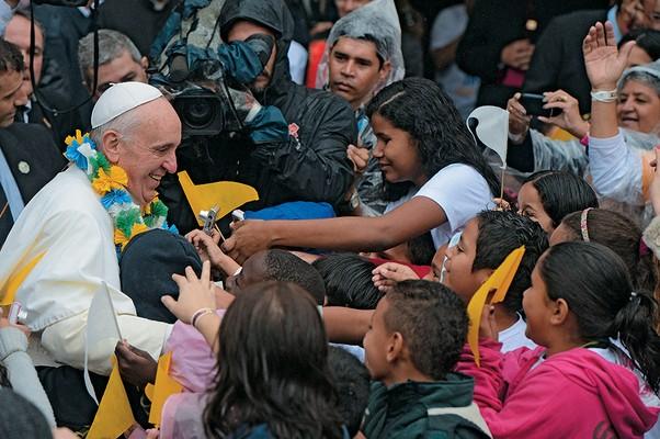 O PASTOR E O REBANHO Francisco cercado por crianças, durante visita a favela no Rio de Janeiro  (Foto:  Yasuyoshi Chiba/AFP)