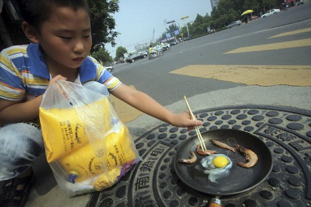Menino fritou um ovo com camarões e uma frigideira colocada em rua em Jinan (Foto: AP)