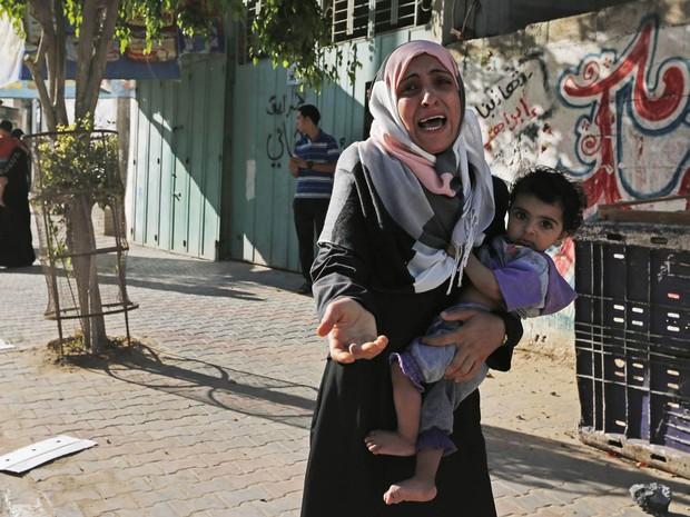 Com o filho no colo, mulher chora após abandonar sua casa com outros palestinos no bairro de Shajaiyeh, na Cidade de Gaza, depois que aviões israelenses despejaram panfletos pedindo que a área fosse abandonada sob risco de bombardeio (Foto: Lefteris Pitarakis/AP)