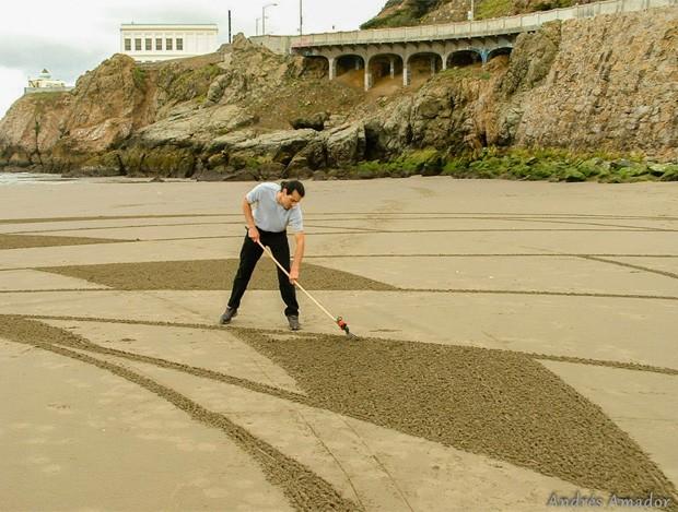 Andres Amador  usa uma espécie de 'vassoura' para diferenciar os tons de cor da areia em seus desenhos (Foto: Reprodução/Facebook/Andres Amador)
