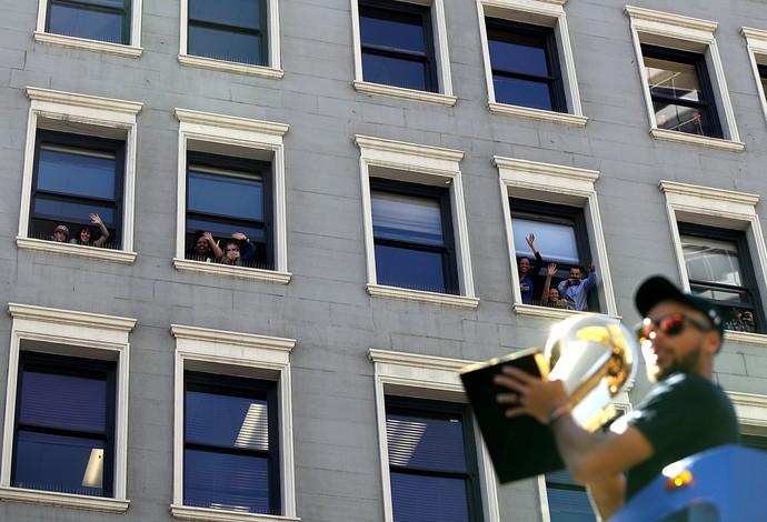 Stephen Curry com o troféu, e fãs acenando de prédio (Foto: Justin Sullivan/Getty Images)