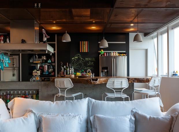 Os detalhes são imprescindíveis no projeto: parede pintada com tinta para lousa permite usar a criatividade e nicho no balcão abriga coleção de bebidas (Foto: Divulgação)