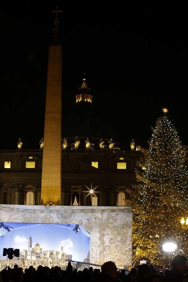 Pessoas observam cena do nascimento de Jesus representada na Praça São Pedro durante a Missa do Galo nesta segunda-feira (24) (Foto: AP)