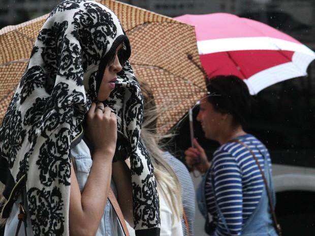 Pedestre se protege da garoa na Avenida Paulista, em São Paulo (SP), na manhã desta terça-feira (21). (Foto: Niyi Fote/Futura Press/Estadão Conteúdo)