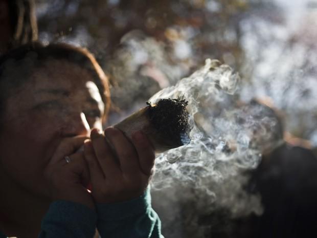 Mulher fuma grande cigarro de maconha durante marcha a favor da legalização, neste sábado, em Santiago, no Chile (Foto: AP Photo/Esteban Felix)
