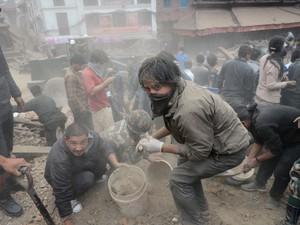 Homem ajuda a limpar o que restou da praça Durbar, patrimônio histórico tomabado pela Unesco, em Katmandu (Foto: Prakash Mathema / AFP)
