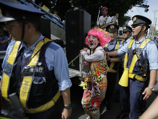 Uma manifestante vestida de palhaço é cercada por policiais em Tóquio durante protesto contra o uso de energia nuclear no Japão. (Foto: AP Photo/Greg Baker)